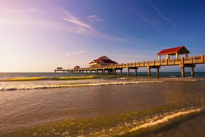 Pier 60 at sunset on a Clearwater Beach in Florida with purple and blue skies, with blue green water with light reflected on it.