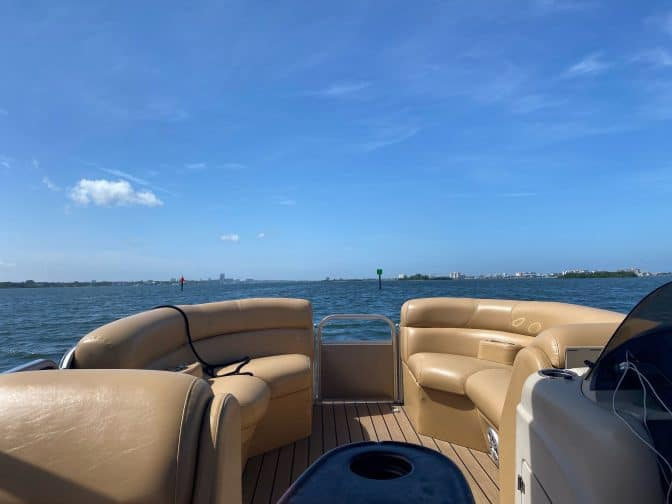 view from a pontoon boat with brown leather seating looking out over the blue bay with blue skies, an example of things to do in Clearwater beach