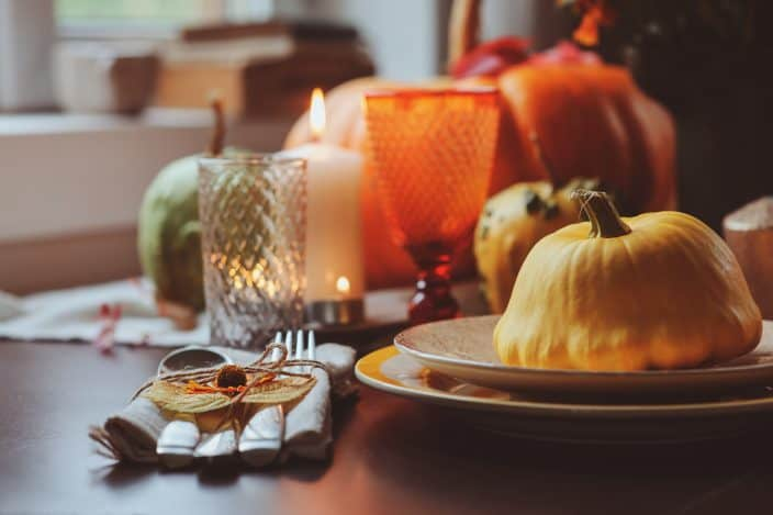An autumn traditional table setting, with white and red candles, a squash sitting on a plate at a place setting and pumpkins on the table, an example of things to do in fall.