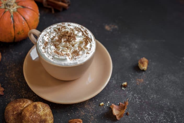 A homemade Pumpkin Spice Latte topped with whipped cream and cinnamon with a pumpkin, snickerdoodle cookie, and spices next to it on a black background.