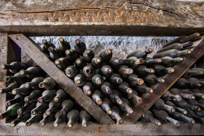 old, dusty wine bottles stack on top of one another in a old wooden shelf with a stone wall behind it