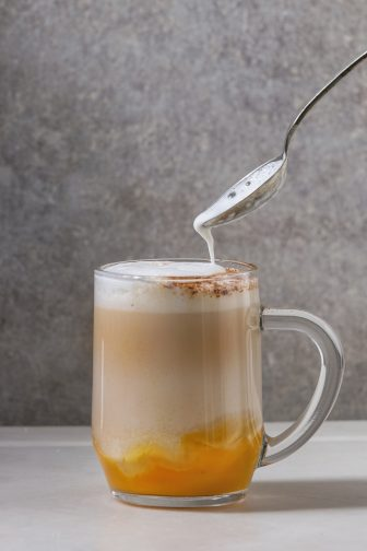 Glass of pumpkin layered spice latte with pumpkin puree, milk foam flowing from spoon and cinnamon standing on white marble table with grey wall at background