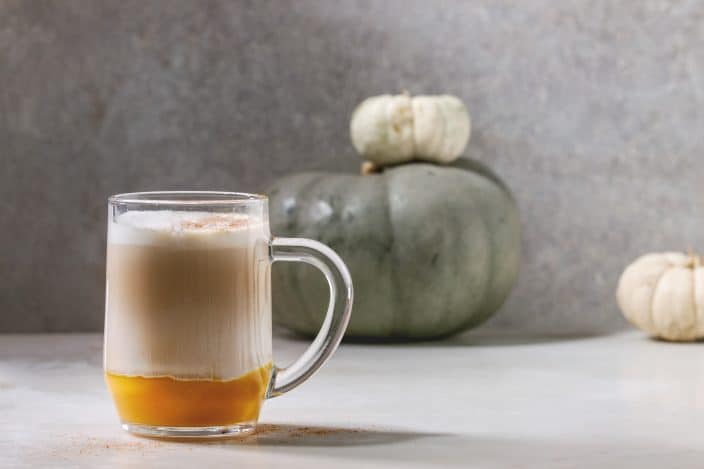 Glass of pumpkin layered spice latte with pumpkin puree, milk foam and cinnamon standing with decorative white pumpkins on white marble table with grey wall at background.