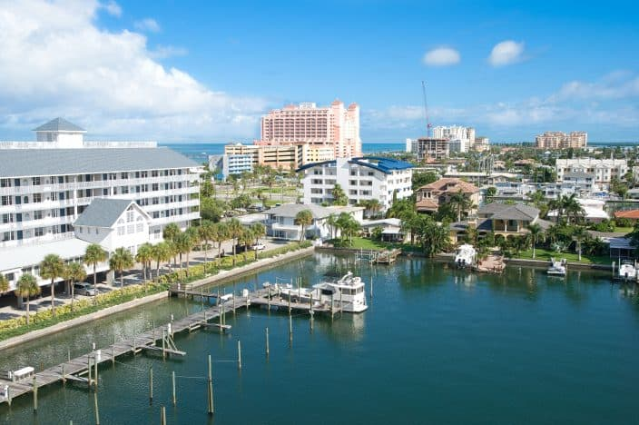 a view of a sunshine afternoon in Clearwater, overlooking the marina, with boats, condos, restaurants, and blue skies