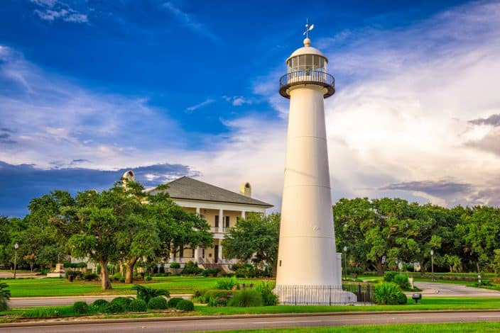 Biloxi, Mississippi USA at Biloxi Lighthouse, with blue skies, green trees and grass, and a yellow mansion in the background, an example of romantic getaways for the weekend