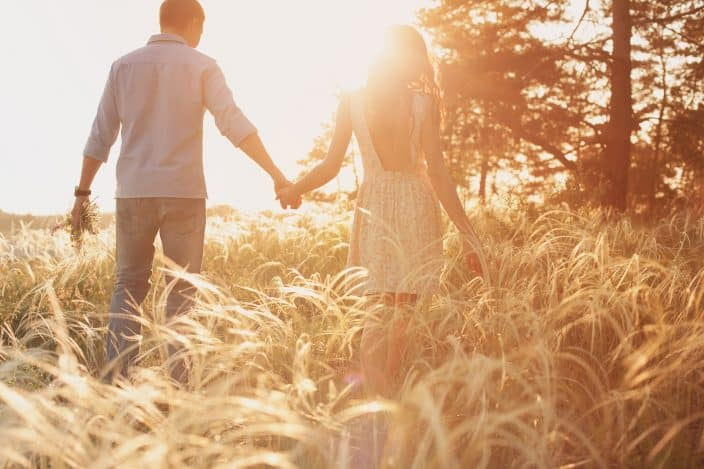 a couple walking in a tall grass field with the sun shining a representation of romantic getaways for the weekend