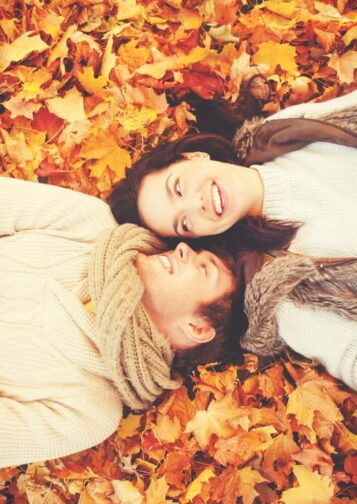 a couple laying in a pile of red, orange, and gold fall leaves on the ground in white sweater and smiling